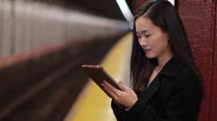 Young Asian woman using tablet pc reading subway platform - stock footage