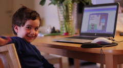 Kid at home wave his hand and turn to his computer screen - stock footage