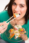 Stock Photo of candid close portrait cute brunette woman raw food sushi lunch