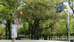 Male basketball player practicing free throws on an outdoor court Stock Footage