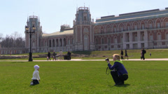 Little girl photograph on grass on a background of historical buildingTsaritsyno Stock Footage