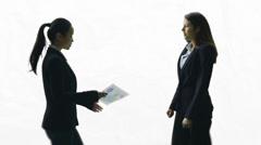 2 businesswomen having a conversation on white background Stock Footage