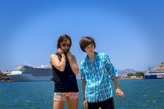 Boy and girl teenager on travel, ocean and big ships in background Stock Photos