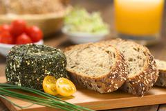 goat cheese with herbs and wholegrain bread - stock photo