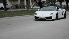 White Lamborghini sports car driving on street speeds pass the camera Stock Footage