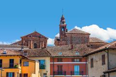 Kirkon kellotorni ja värikkäitä taloja La Morra. Kuvituskuvat