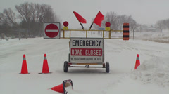 Road closed sign due to snow storm and blizzard conditions ahead Stock Footage