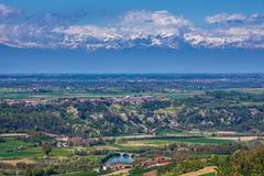 Green valley and snowy mountains in piedmont, italy. Stock Photos