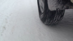 Shot of snow tires driving on snow in winter storm Stock Footage