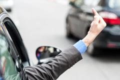 Man showing middle finger from car window - stock photo