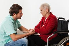 young nurse assisting disabled lady - stock photo
