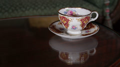 Historic Antique Tea Cup and Saucer on Glass Table in a Victorian Parlor Stock Footage