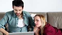 Beautiful young happy couple relaxing and bonding on couch - stock footage