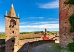 Bell tower and medieval brick wall in small italian town. Stock Photos