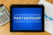 Stock Photo of partnership word on digital tablet