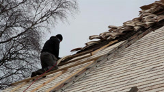 A roofer nailing some wooden shingles Stock Footage