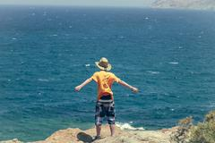 Male teenager standing on a cliff with blue ocean in background Stock Photos