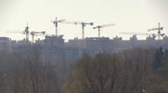 Tower cranes on a background of urban development and nature park Stock Footage