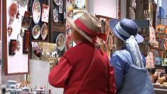 Two women in straw hats, watching  traditional ceramic plates in shop windows Stock Footage