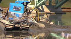 Floating Excavator amphibian works on water drags the ground from the bottom Stock Footage