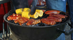 Meat and corn and ribs roasted on a barbecue outdoors Stock Footage