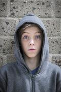 Portrait of a male teenager with wide eyed in front of a wall Stock Photos