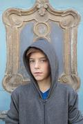 portrait of a male teenager with gray hoody in front of a ornamental door - stock photo