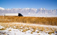 Semi truck speeding down utah highway winter wasatch mountains Stock Photos
