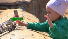 Young girl play and throws out of playground toy car - stock footage