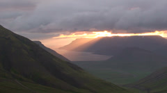Midnight sunshine under cloud cover in fjords Stock Footage