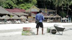 Fishermen carrying food from their boat to the beach (Malaysia) Stock Footage