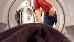 Inside view from dryer of being loaded by a male figure, tumbling, and unloaded. Stock Footage