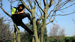Cute teenager reading ipad tablet sitting on tree dolly shot - stock footage
