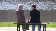 Two elderly women sitting on a bench on a background of lake and talking - stock footage
