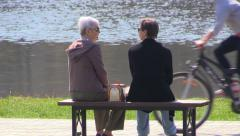 Two elderly women sitting on a bench on a background of lake and talking Stock Footage
