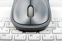 A wireless mouse placed on laptop keyboard - stock photo