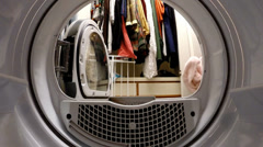 Inside view from dryer of being loaded by a woman, tumbling, and unloaded. - stock footage