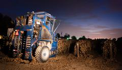 night time agriculture fruit harvest grape harvesting machine food picker - stock photo