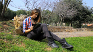 Female teenager reading ipad tablet in park happy Stock Footage