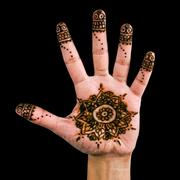 Henna design on the palm of the hand - isolated in black - stock photo