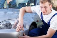 Stock Photo of mechanic repairing car scratching