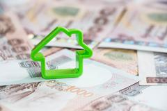 Small house on Thailand money background - stock photo