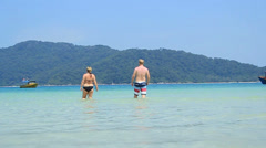 Tourists walking in water (Malaysia - Perhentian islands) Stock Footage