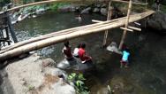 Children bathe  mountain in river under bamboo bridge Stock Footage