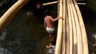 Boy crosses bamboo bridge over mountain river Stock Footage