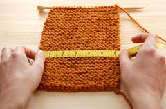 Two hands measuring knitting in inches - stock photo