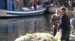 Fishermen rearranging nets Stock Footage