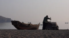 A worker repairing his wooden fishing boat at beach Stock Footage