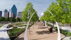 Aerial from under arches to skyline above Dallas Klyde Warren Park Stock Footage