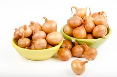 Two bowls full of onions on a white background Stock Photos